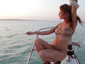 Sexy dark haired shows off her sexy assets while sailing on a boat