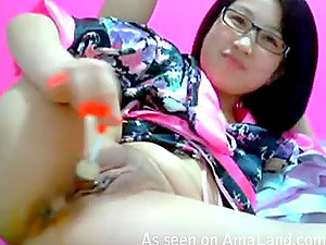 A kinky Asian bitch masturbates with a lollipop on the couch