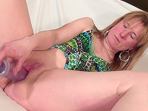 Dutch housewife shoves the fake penis deep into her hairless snatch