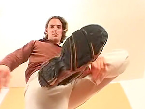 A long haired hunk dude takes shoes off and rubs feet