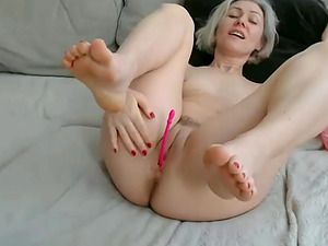 Sexy slut with gray hair teases with legs spread wide open exposing her hairy pussy