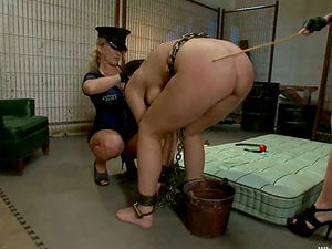 Chained dark-haired gets whipped and toyed by a policewoman