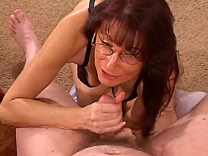 Mature dark haired kneels in front of a man to suck his schlong