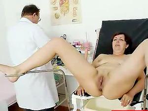 Mature black-haired chick shows her vagina at medical examination
