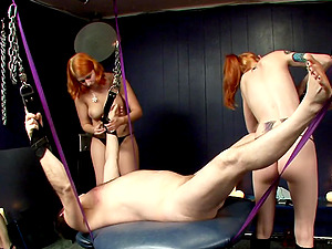 Two red-haired mistresses crush a man's ball sack in Cock and ball torture movie