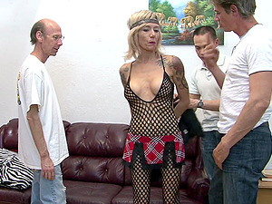 Mature hippie with ink serves three horny guys in a gang-fuck