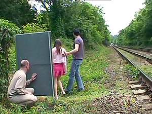 A man strokes off while watching a duo fucking outdoors