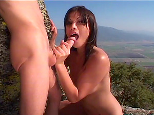 On a cliff this bombshell is dual penetrated by two guys
