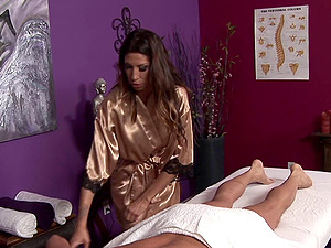 Beauty in a shiny satin bathrobe caresses and blows him on the table