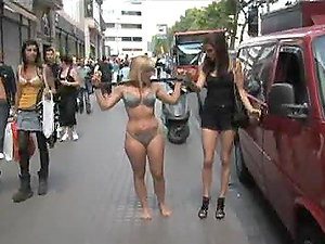 Hot Blonde Ambling In the City in Swimsuit with a Spar on Her Back
