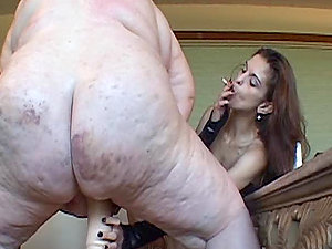 Dark haired domme makes a fat lesbo suck a faux-cock