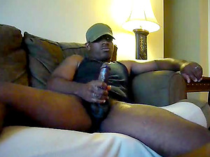 Straight beefy black hunk jerks off and shots a big load watching porn on the couch.