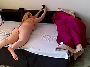 She observes and films her own masturbation with her phone.