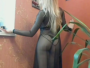 Blonde woman in see through dress teases while standing next to a window