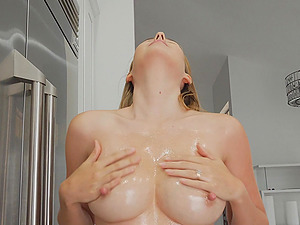 Solo blonde model Aali oils up her huge tits and erect nipples