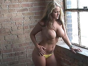Blonde ultra-cutie Michelle Moore poses for the web cam near a brick wall