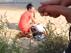 horny guy masturbates at the beach while horny lady watches him
