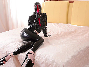 Costumed Lucy Latex masturbates alone using her hand and red dildo