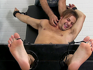 Handsome guy laughs and moans from tickling by an older dude