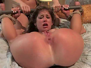 Hog tied woman gets toyed by two sexy chicks in a bedroom